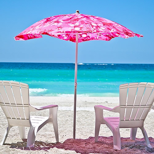 Chairs by the beach with pink umbrella image