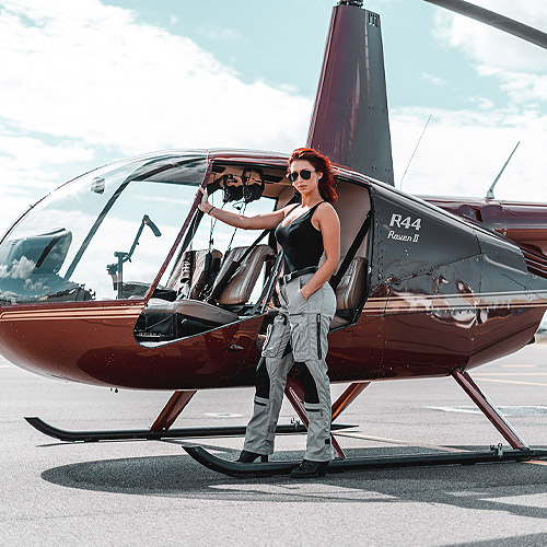 Photo of a woman standing by a helicopter